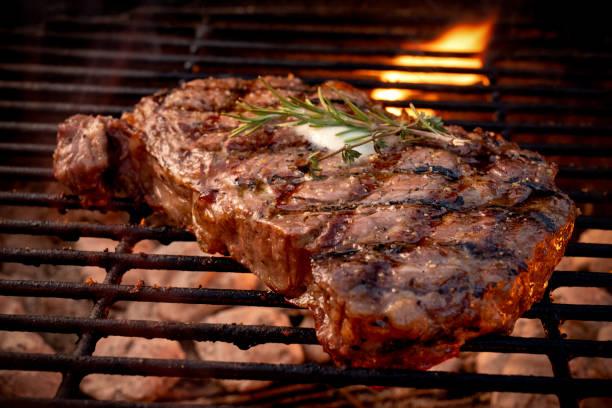 duży soczysty wołowina rib eye steak na hot grill z węglem drzewnym i płomieniami - grillowany zdjęcia i obrazy z banku zdjęć