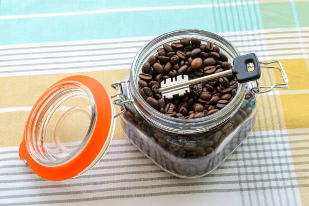 großer schlüssel in einem clip-top-glas mit kaffeebohnen auf einer tischdecke. kann für massennahrungsmittel als cache oder sicher. um etwas zu verbergen. schlüssel zu einem glaskonzept. - topfdeckel speicher stock-fotos und bilder