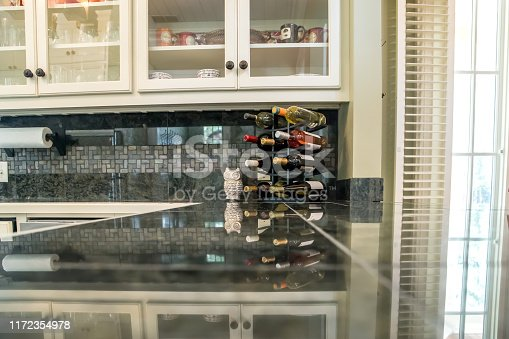 large kitchen granite counter with wine rack storage and bottles