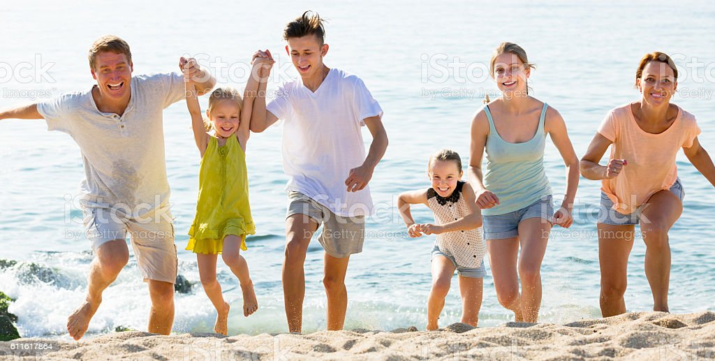 Large laughing family on beach on sunny day stock photo