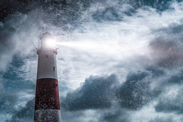 grand phare avec la lumière lumineuse de recherche sur une nuit sombre et orageuse - phare photos et images de collection