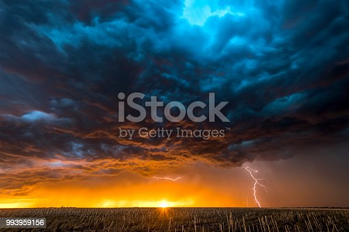 A nighttime, tornadic mezocyclone lightning storm shoots bolt of electricity to the ground and lights up the field and dirt road in Tornado Alley.  A large lightning strike at dusk in an open plain framed against a deep, dark orange sunset and stormy skies.   A large lightning strike at dusk in an open plain framed against a deep, dark orange sunset and stormy skies.
