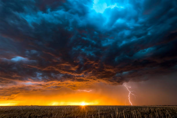 Large lightning strike at dusk on Tornado Alley A nighttime, tornadic mezocyclone lightning storm shoots bolt of electricity to the ground and lights up the field and dirt road in Tornado Alley.  A large lightning strike at dusk in an open plain framed against a deep, dark orange sunset and stormy skies.   A large lightning strike at dusk in an open plain framed against a deep, dark orange sunset and stormy skies. atmospheric mood stock pictures, royalty-free photos & images