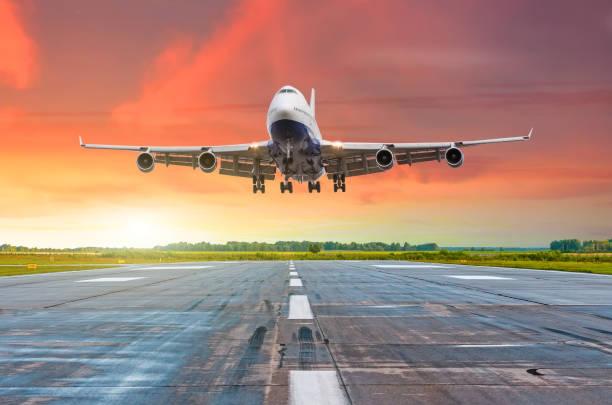 grandes aeronaves de largo recorrido con cuatro motores de vuelo de llegada en una pista de aterrizaje en la noche durante una puesta de sol rojo brillante. - aterrizar fotografías e imágenes de stock