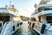 Large luxury yachts moored in the port of a tourist Mediterranean city in sunset light