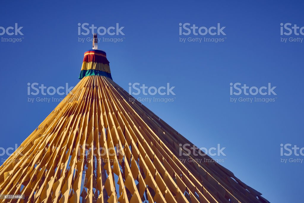Large mast with prayer flags vibrating in the wind - Buddhist Temple Chagdud Gonpa Khadro Ling of Três Coroas. stock photo