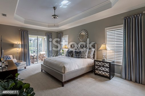 Large master bedroom interior in Southwest Florida home.  There is a large gray bed covered with a white bedspread.  There are furnishings and a green plant in the room, and the walls and curtains are gray.
