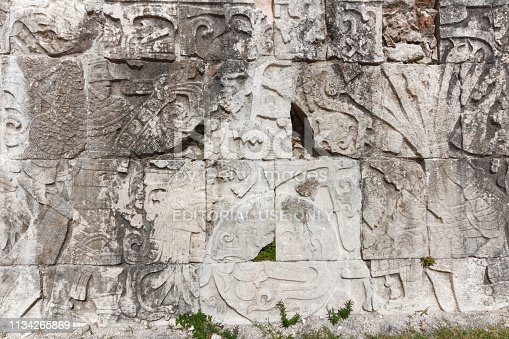 Chechen Itza, Mexico - April 30 2013: Close up of a large Mayan stone carving along the bottom of a wall in Chechen Itza, Yucatan, dating between AD 900 and 1050. The carving, in relief, shows a standing figure on the right holding a sword or knife. Below him is a severed head. in the centre of the panel is a decorated circle congaing a large skull with an open mouth. To the left of the panel are kneeling figures wearing feathered headdresses.