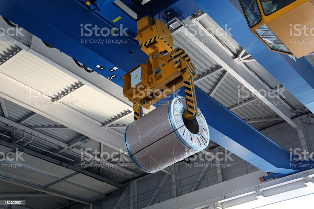 A large mechanical crane with a huge steel coil stock photo