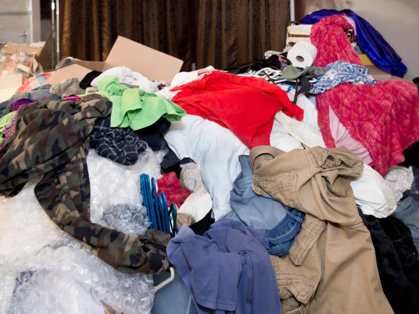 Large messy pile of household items, clothes, boxes, hangers, bubble wrap, toilet paper, pants, shirts, dresses with curtains and mirror in background Close up color photo of extremely messy and disorganized room full of clothing items and random household things including tops, shorts, hangers, boxes, toilet paper, packing materials, bubble wrap, curtains greed stock pictures, royalty-free photos & images