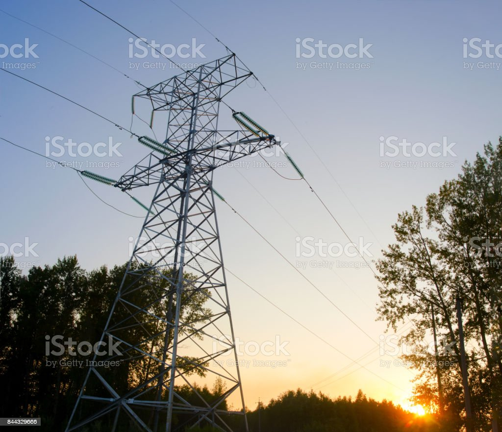 A large metal anchor the tower to the backbone transmission line is a semi sideways on the back of the solar disk at sunset in a field between trees with garlands of high-voltage insulators and wires. stock photo
