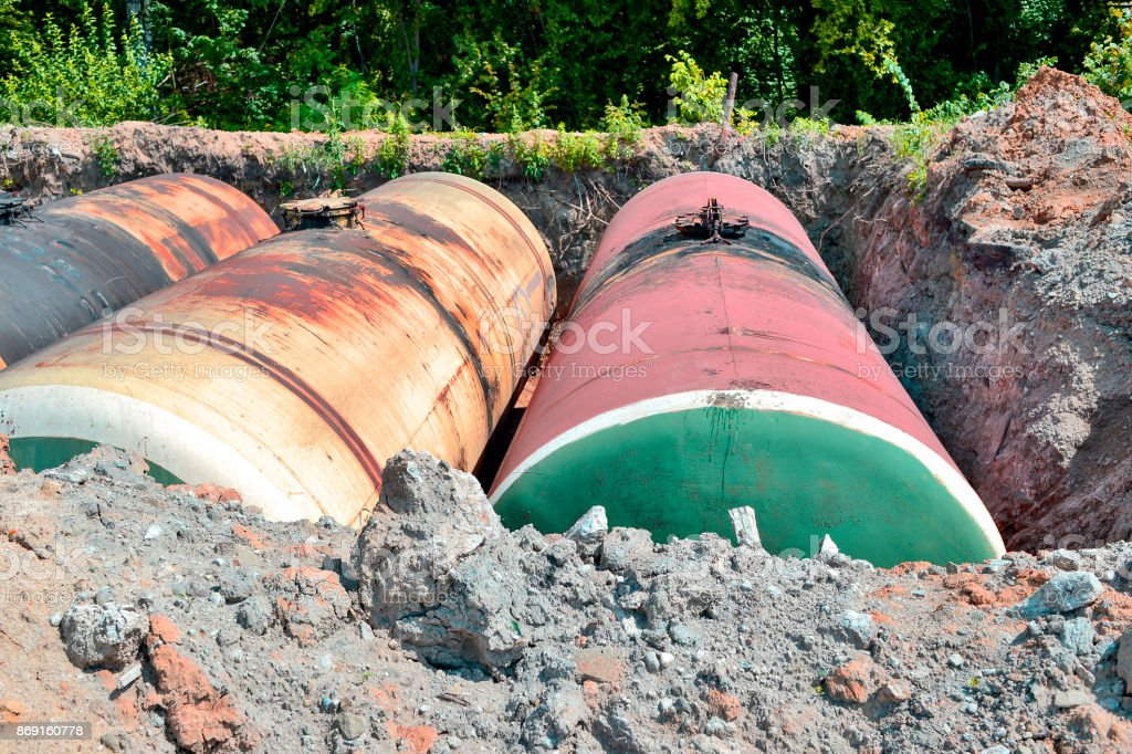 Large metal tanks are buried in the ground in the production warehouse stock photo