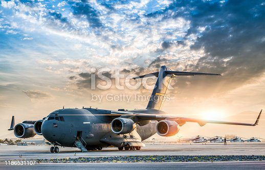 Large military transport aircraft at sunset.