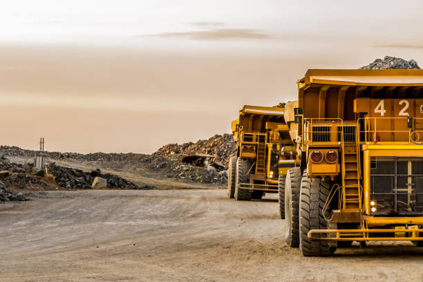 Large mining rock dump trucks transporting Platinum ore for processing stock photo