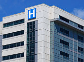 istock large modern building with blue letter H sign for hospital 1240772668