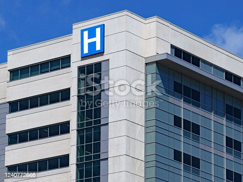 large modern building with blue letter H sign for hospital