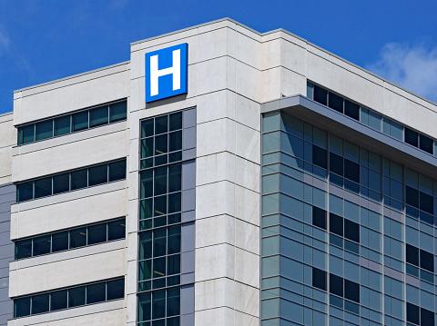 large modern building with blue letter H sign for hospital