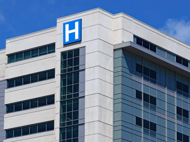 großes modernes gebäude mit blauem buchstaben h zeichen für krankenhaus - krankenhaus stock-fotos und bilder