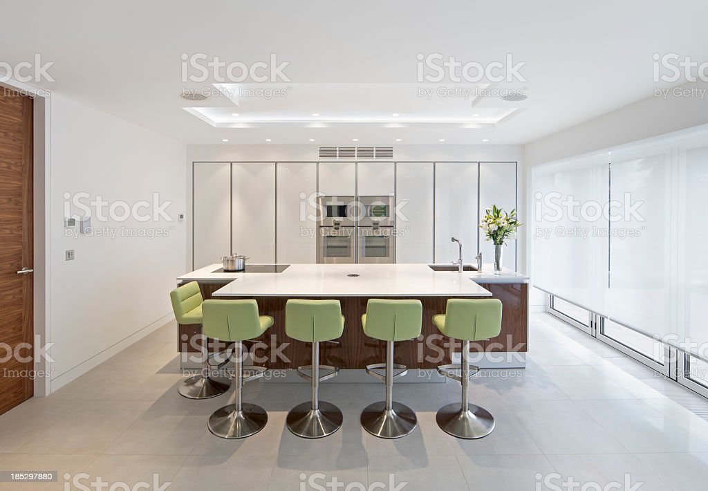 Large modern kitchen with green chairs stock photo