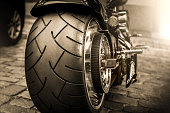 Hamburg, Germany - September 13, 2015: Close up of a parked motor cycle in Hamburg City. A close up shot from behind of the extrem big tire profil. Maybe it is a Harles Davidson motorcycle. This image is processed in raw and sepia toned, taken with a 50 mm prime lens with full format camera in daylight