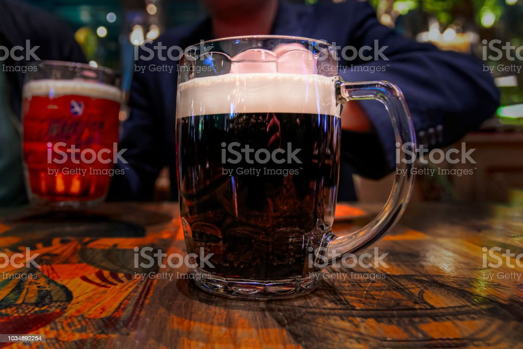Large mug of dark beer with white foam on  vintage wooden table. stock photo