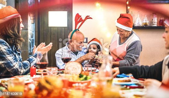 1064325668 istock photo Large multi generation family having fun at christmas supper party - Winter holiday x mas concept with parents and children eating together opening gifts at home - Focus on grandpa and daugther hands 1187400619