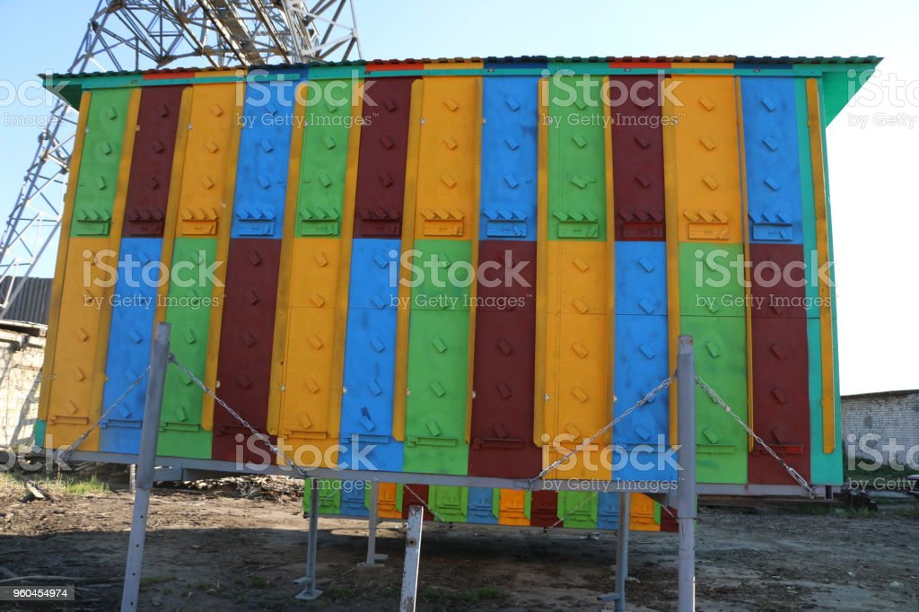 large multi-colored mobile apiary for 48 hives. wooden house for bees. stock photo