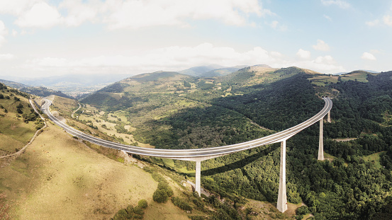 A large, high multiple lane highway viaduct in a beautiful green valley
