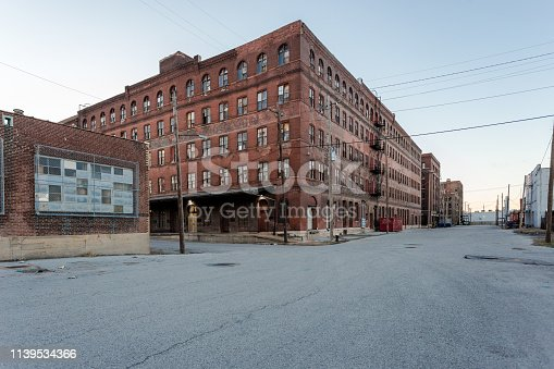 Large multiple story vintage red brick industrial warehouse ready for development in a depressed urban area at dusk