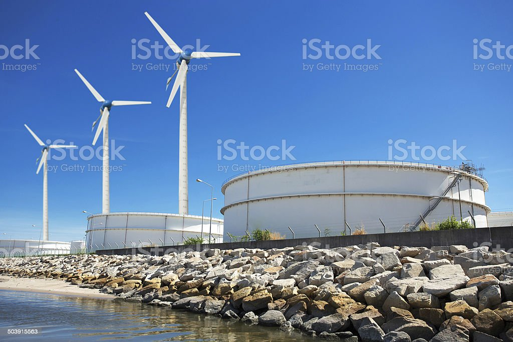 Large natural gas storage tanks with a windmill. stock photo