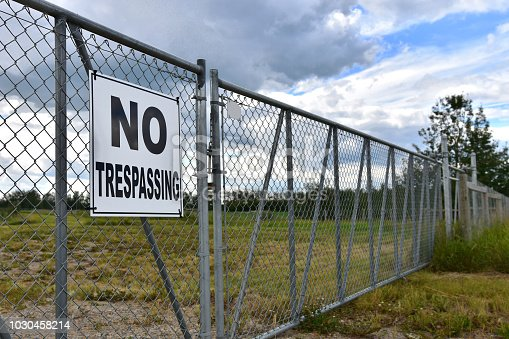 An image of a large black and white no trespassing sign posted on a security gate.