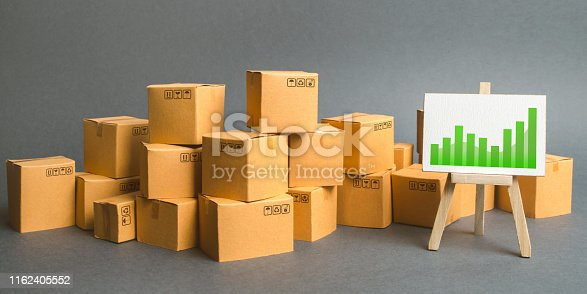 1155852718istockphoto A large number of cardboard boxes and sign with green positive trend chart. rate growth of production of goods and products, increasing economic indicators. Increasing consumer demand. Trade balance 1162405552