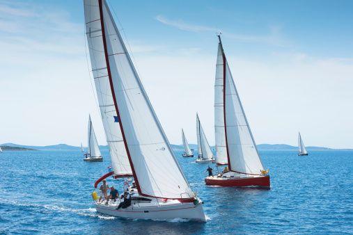 Front view of large number of sailboats sailing against the wind using main sail and genoa, Adriatic sea, Europe