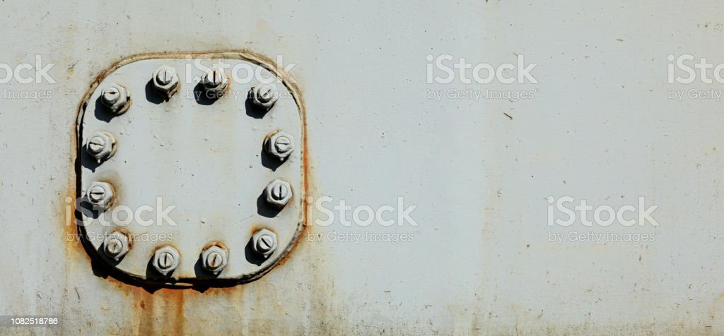 Large Nuts And Bolts On Gray Steel Plate Of Rail Bridge Lit By