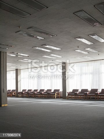 Large old lounge. Retro style interior. Columns and rows of armchairs.