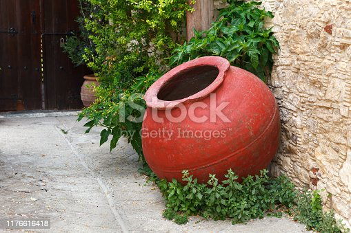 Large, old, red amphora on the street of the wine village. The design element of the street