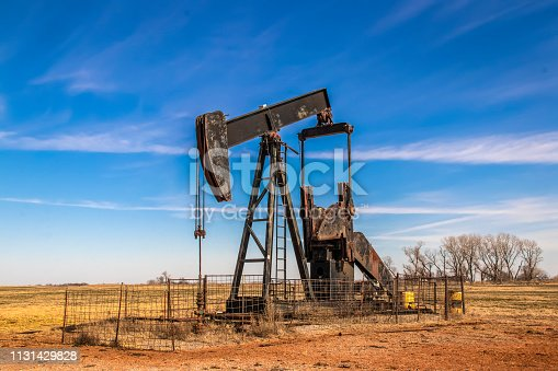 Large old rusty oil well pump jack surrounded by cattle panel fence out in field with very blue sky in winter.