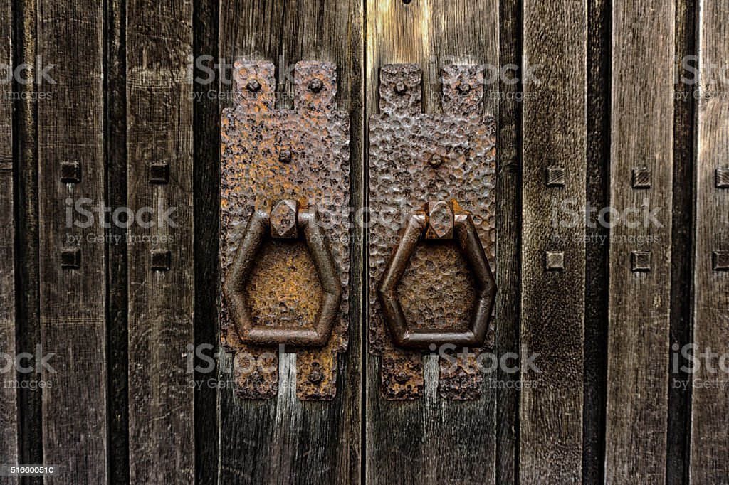 Large old  wooden doors with iron decorative handles stock photo