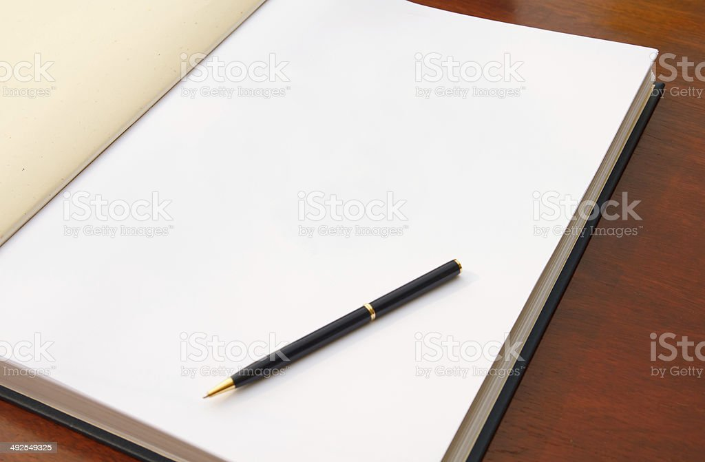Large open book on wooden table with a pen. stock photo