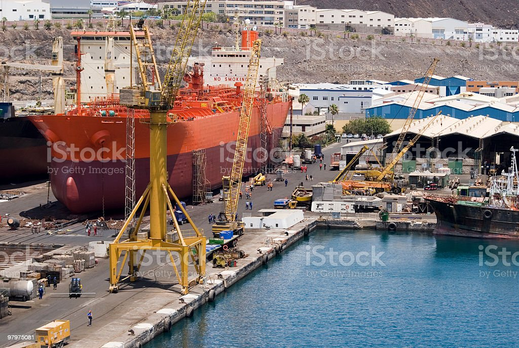 Large orange and red container ship being worked on in dock royalty-free stock photo
