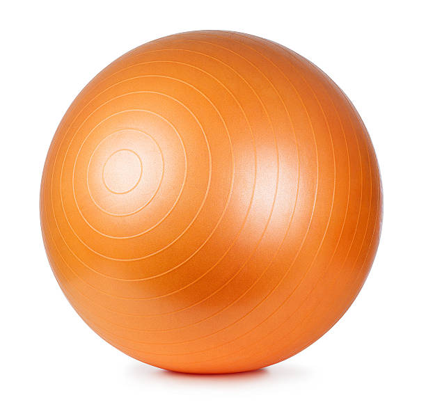 a large orange fitness ball on a white background - ball stock photos and pictures