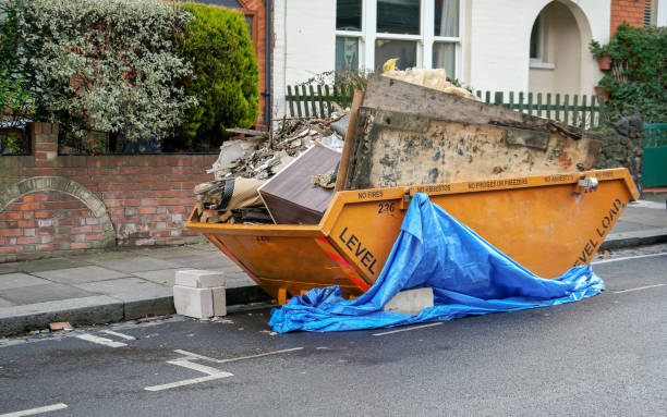 Large orange metal skip container in front house, full of rubbish from household reconstruction stock photo