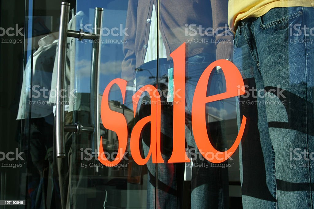 Large orange sale sign on a clothes shop royalty-free stock photo
