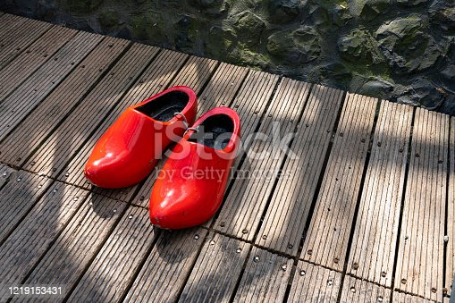 Large red ornamental clogs on wooden decking
