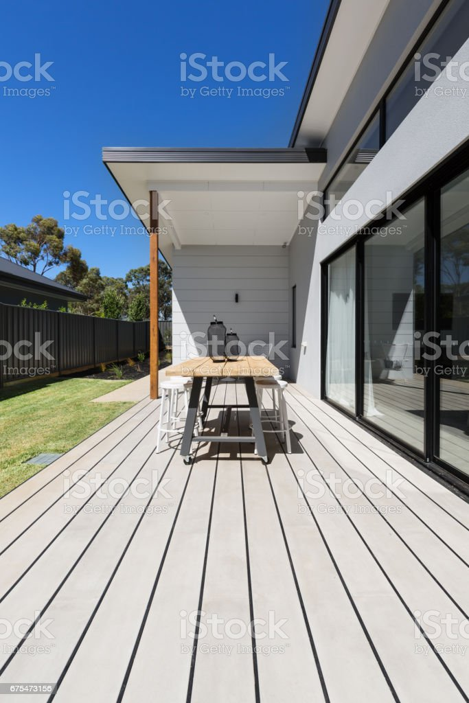 Large outdoor decking and high entertaining table in a contemporary...