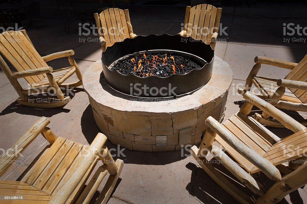 Large outdoor fire pit surrounded by wooden rocking chairs stock photo