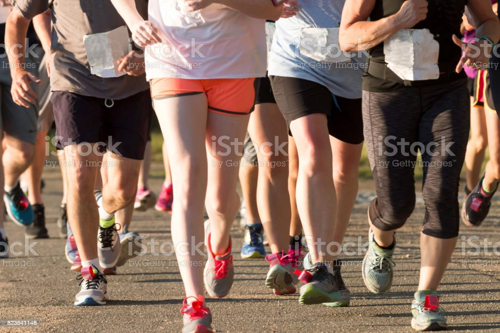 Large pack of runners during a 5K race stock photo