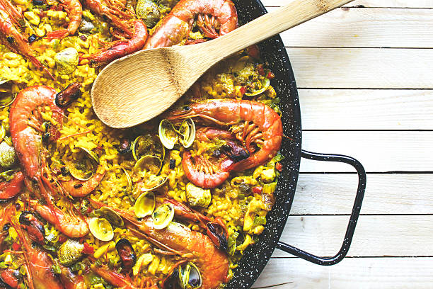 large pan of rice with seafood paella - paella stock photos and pictures