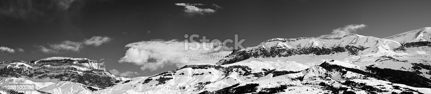 Large panorama of high snowy mountains and sky with clouds at sun winter day. Caucasus Mountains, Shahdagh, Azerbaijan. Black and white toned landscape.