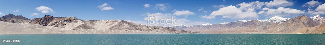 Large panorama of landscape near Bulunkou River, at the Karakorum Highway (Xinjiang Province, China). Sand dunes & snow-capped mountains. Breathtaking landscape.